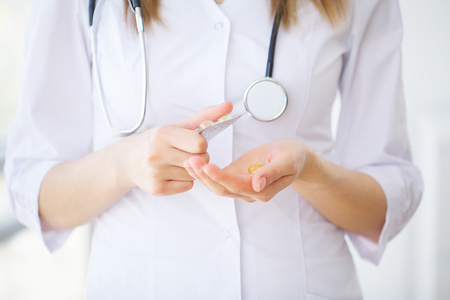 Doctor holding pills on hand. Medicine and health care concept Stock Photo