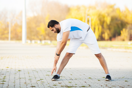 Fitness. Stretch man doing stretching exercise. Standing forward bend stretches of legs Stock fotó