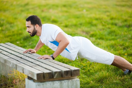 Fitness. Push-up exercise fitness man training arms muscles at outdoor gym Stock Photo