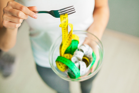 Diet and Weight Loss. Woman holds bowl and fork with measuring tape 스톡 콘텐츠