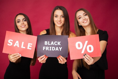Shopping. Three women holding discount blank on red background in black friday holiday Stock fotó