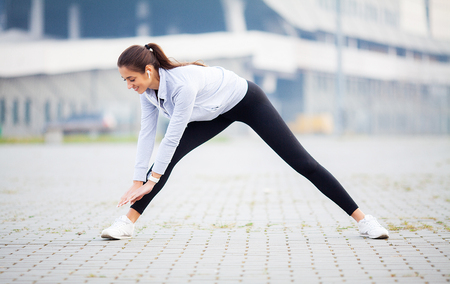 Fitness woman doing workout standing in a stadium background Standard-Bild