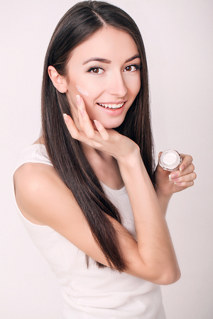 Applying cosmetic cream. A beautiful young woman applying face moisturizer. Scine care of the face and hands