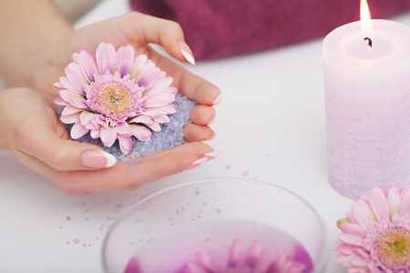Spa Procedure. Woman In Beauty Salon Holding Fingers In Aroma Bath For Hands. Closeup Of Female Nails Soaking In Bowl Of Water With Pink Flower Petals. Aromatherapy. High Resolution