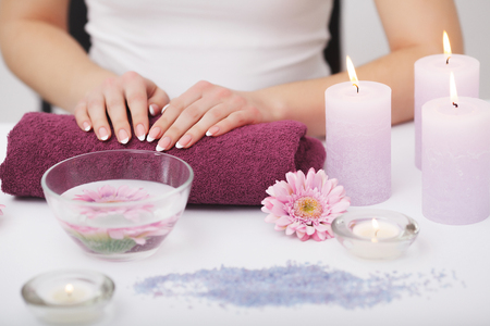 Spa Beauty Salon. Closeup Of Female Hands With Perfect Natural Fingernails Soaking In Hand Bath Before Manicure. Woman Washing Perfect Nails In Transparent Bowl Of Water. Nail Care. High Resolution Stockfoto