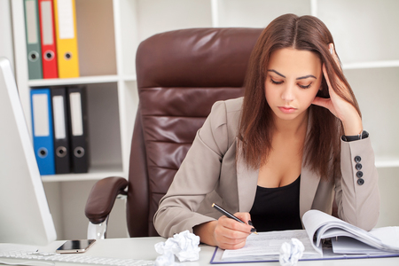 Young boring businesswoman sitting at the table with laptop and want to sleep while yawn at workplace in modern office.