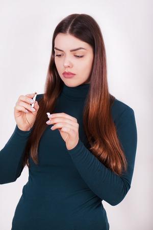 Beautiful Woman Holding Broken Cigarette. Quitting Cigarettes