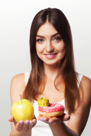 Diet. Emaciation. Girl smiles while holding an apple in her arms. Sports and fitness. The concept of health and beauty. On a gray background.