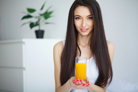 Woman drinking orange juice in bedroom Stock Photo
