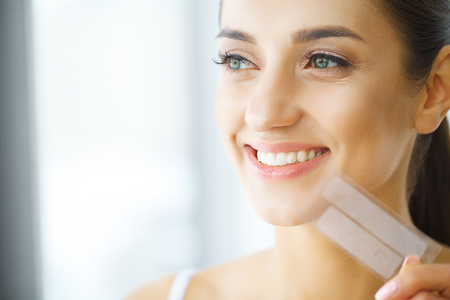 Teeth Whitening. Beautiful Smiling Woman Holding Whitening Strip. High Resolution Image