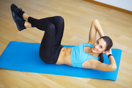 Side view of fit woman doing plank core exercise.