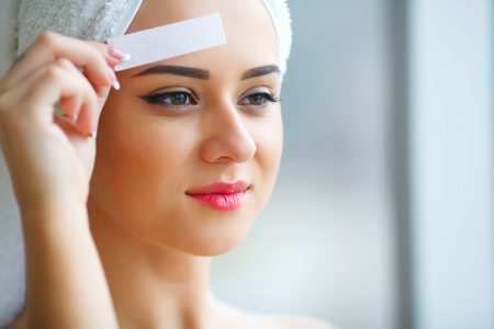 Young beautiful woman makes wax eyelids in her bathroom.