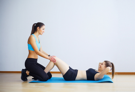 Young woman exercising sit-ups with assistance of female friend in gym. 写真素材 - 115023379