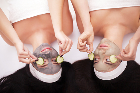 Home spa. Two beautiful young women holding pieces of cucumber on their eyes and smiling while on the bed