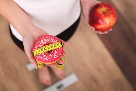 Diet. Woman Measuring Body Weight On Weighing Scale Holding Donut and apple. Sweets Are Unhealthy Junk Food. Dieting, Healthy Eating, Lifestyle. Weight Loss. Obesity. Top View Archivio Fotografico