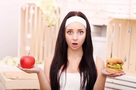 A young girl sits at home and makes a choice between healthy food and hamburger Standard-Bild - 114988301