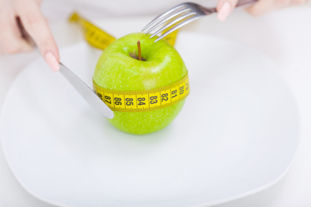 Diet. Apple and centimeter on the plate. Fitness healthy eating