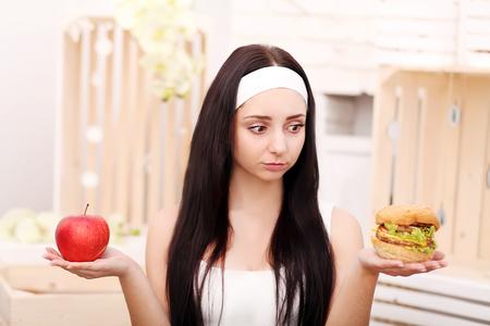 A young girl sits at home and makes a choice between healthy food and hamburger Standard-Bild - 114988252