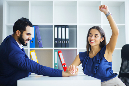 Man and woman doing arm wrestling in office