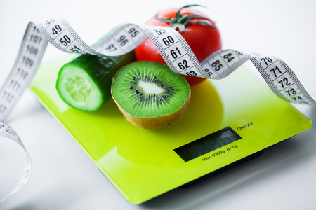 Diet. Fruits and vegetables with measuring tape on weight scale Imagens