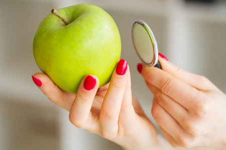 Health. Healthy Eating. The nutritionist holds in the hands of Fresh Green Apple. Fresh Vegetables and Fruits on the Table. Happy Doctor. High Resolution. Stock Photo