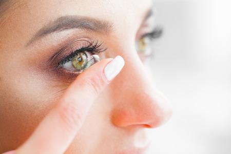 Gesundheit und Schönheit. Schönes junges Mädchen mit grünen Augen hält Kontaktlinse am Finger. Augenpflege. Gute Sicht Frische Sicht. Hohe Auflösung Standard-Bild