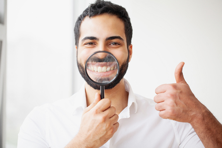 Businessman with magnifying glass zooming on his smile Stock Photo
