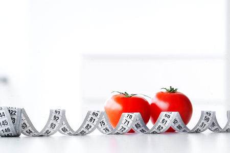 Diet. Fitness and healthy food diet concept. Balanced diet with tamatos measuring tape on white background. Closeup