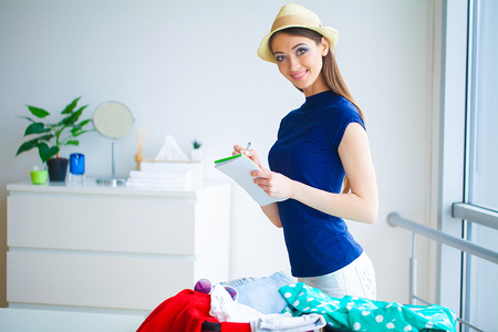 Vacation. Woman Who is Preparing for Rest. Young Beautiful Girl Sits on the Bed. Portrait of a Smiling Woman. Happy Girl Goes On Vacation Stock Photo