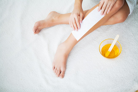 Waxing. Beautician Waxing Womans Leg In Spa Salon 免版税图像