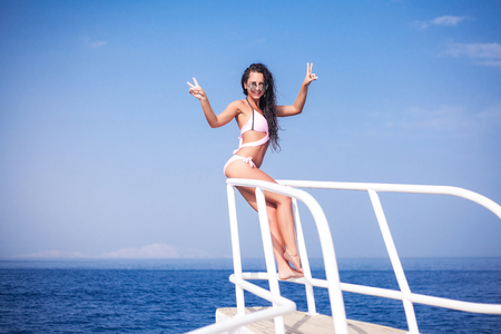 A young woman admires the sea from the deck of a ship. Sea cruise, travel and vacation, round-the-world trip Stock Photo