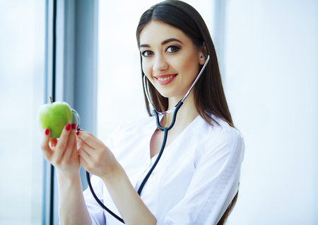 Health and Beauty. Doctor Dietitian Standing near the Window at the Light Office. Girl Holds Apple in Hands And Smiles. Doctor Shows Apple Stock Photo