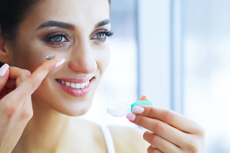 Health and Beauty. Beautiful Young Girl with Contact Lenses. Woman Holds Green Contact Lens on Her Finger. Healthy View. High Resolution 免版税图像