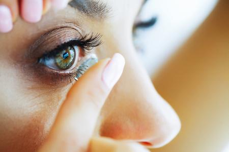 Gesundheit. Schönes junges Mädchen hält eine Fingerkontaktlinse. Porträt einer schönen Frau mit grünen Augen. Gesundes Aussehen. Hohe Auflösung