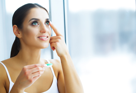 Health and Beauty. Young Woman Applying Contact Lenses. Fresh View. Portrait of a Beautiful Woman with Green Contact Lenses. High Resolution Standard-Bild