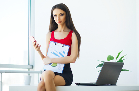 Business. Portrait of a Young Woman holding a Blue Folder Hand. Dressed in Red T-shirt and Black Skirt. Business Woman Sitting on the Tables in the Light Modern Office. High Resolution