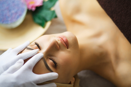 Beauty and Care. Young Woman Lying On Massage Tables In Spa Salo