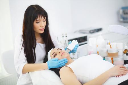Woman having facial treatment in beauty salon Standard-Bild