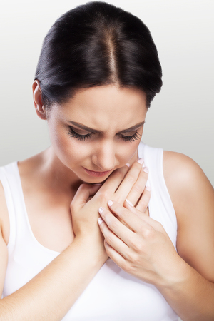 Sore throat. The girl holds her arms in the throat. Cold. Angina. Painful condition. The concept of health. On a gray background.