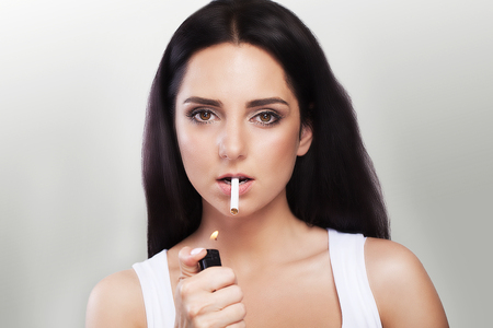 Bad habit. Beautiful woman lighting a cigarette in her mouth. Portrait of a young woman. The concept of smoking. On a gray background.