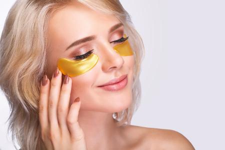 Parche debajo de los ojos. Rostro de mujer hermosa con parches de hidrogel dorado, máscara de colágeno antiarrugas de elevación en la piel facial fresca y saludable. Alta resolución