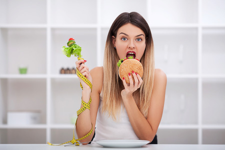 Diet. The concept of healthy and unhealthy nutrition. The model plus size makes a choice in favor of healthy food and fruit by refusing fast food and burger. XXL woman Banque d'images - 115898008