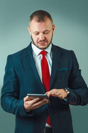 Cheerful confident businessman holding a digital tablet, he is using apps and connecting to the internet