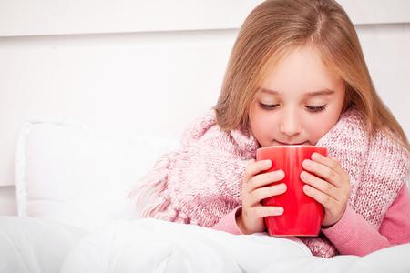 Flu. Sick little girl with hot lemon tea