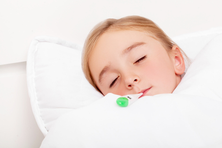 Flu. Young girl lying in bed with a thermometer Imagens