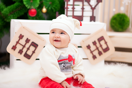 Cute little girl dressed as snowflakes near the Christmas tree and decorations Archivio Fotografico