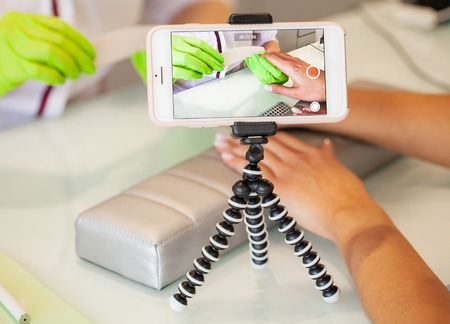 Manicure procedure video videoshooting on phone. Skillful master of manicure holding file in her hands while working in her beauty salon