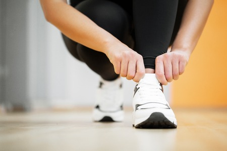 Fitness woman tying sneakers rope. Sportswear and Fashion theme