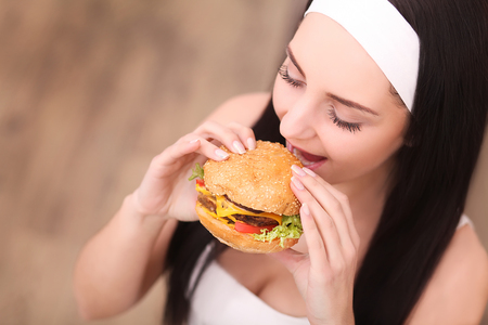 Unhealthy eating. Junk food concept. Portrait of fashionable young woman holding burger and posing over wood background. Close up. Copy-space. Perfect hair, skin, make-up and manicure. Studio shot