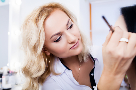 Make-up artist does makeup to a beautiful girl in a beauty salon